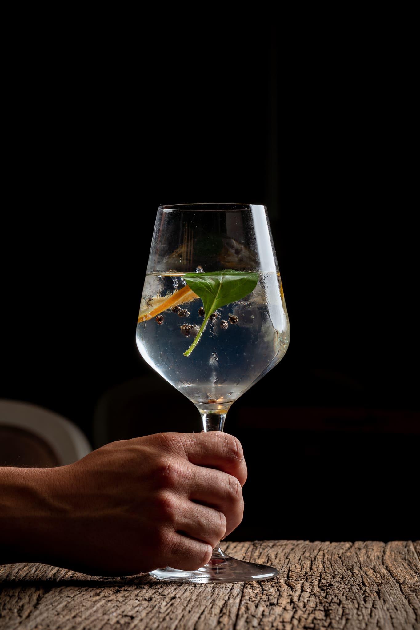 Main tenant un verre à pied avec un cocktail dedans